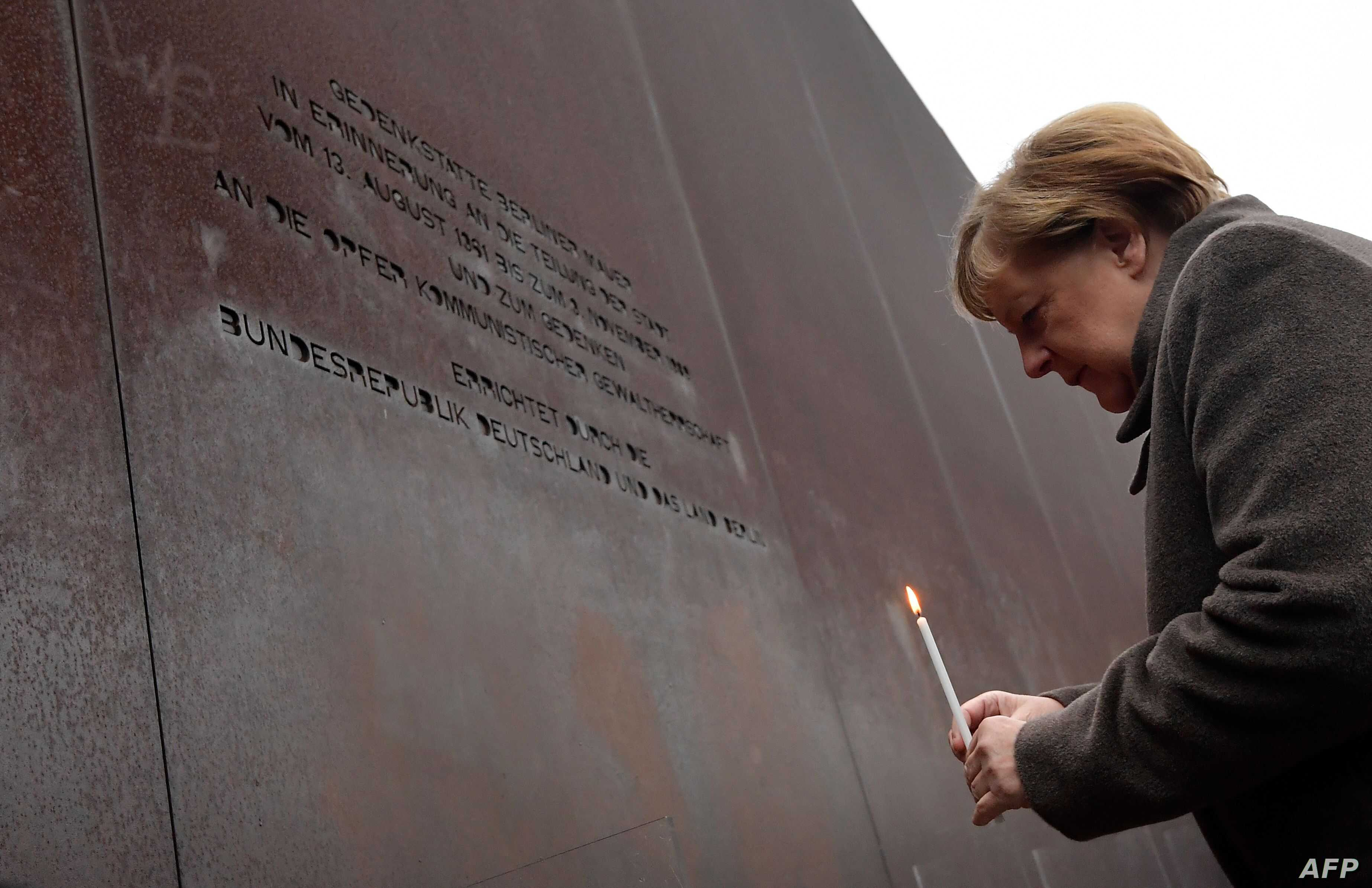 German Chancellor Angela Merkel places a candle at the Berlin Wall Memorial during the central commemoration ceremony for the…