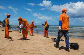 Municipality workers clean oil at a beach in Lauro de Freitas, Bahia state, Brazil, on November 2, 2019. - The beaches of…