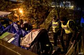 French police talk to migrants during an evacuation operation in Paris on November 7, 2019. - More than a thousand migrants and…