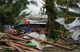 A resident looks at a house damaged at the height of Typhoon Phanfone in Tacloban, Leyte province in the central Philippines on…