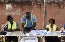 TOPSHOT - An electoral worker sorts ballots during the counting of votes for Guinea-Bissau's presidential runoff on December 29…