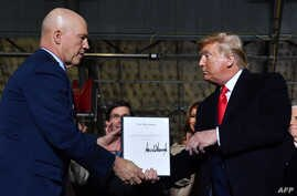 "US President Donald Trump (R) hands US General John W. Raymond a document after signing the ""National Defense Authorization Act…"
