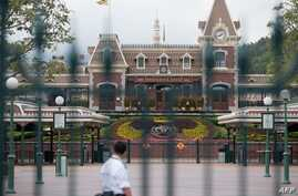 A security guard checks a empty square usually filled with visitors at Hong Kong Disneyland in Hong Kong on January 26, 2020,…
