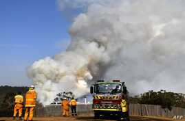 Firefighters work as smoke rises from a bushfire in Penrose, in Australia's New South Wales state on January 10, 2020. - High…