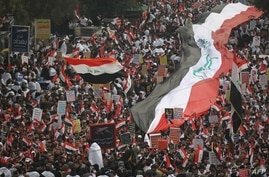 TOPSHOT - Thousands of Iraqis, waving national flags, take to the streets in central Baghdad on January 24, 2020 to demand the…
