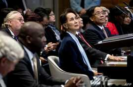 (FILES) In this file photo taken on December 11, 2019 Myanmar's State Counsellor Aung San Suu Kyi (C) stands before the UN's…