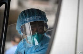 An ambulance driver, wearing protective clothing to help stop the spread of a deadly SARS-like virus which originated in the…