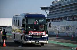 """A bus with slogans written in Chinese """"Go, we go back to home"""" transfers passengers from the Diamond Princess cruise ship, in…"""