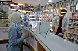 People wearing protective masks shop at a pharmacy in the Iranian capital Tehran on February 24, 2020. - Iran's government…