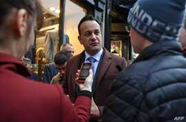 Ireland's Prime Minister and leader of the Fine Gael party, Leo Varadkar (C), talks with a young man about Brexit, as he…