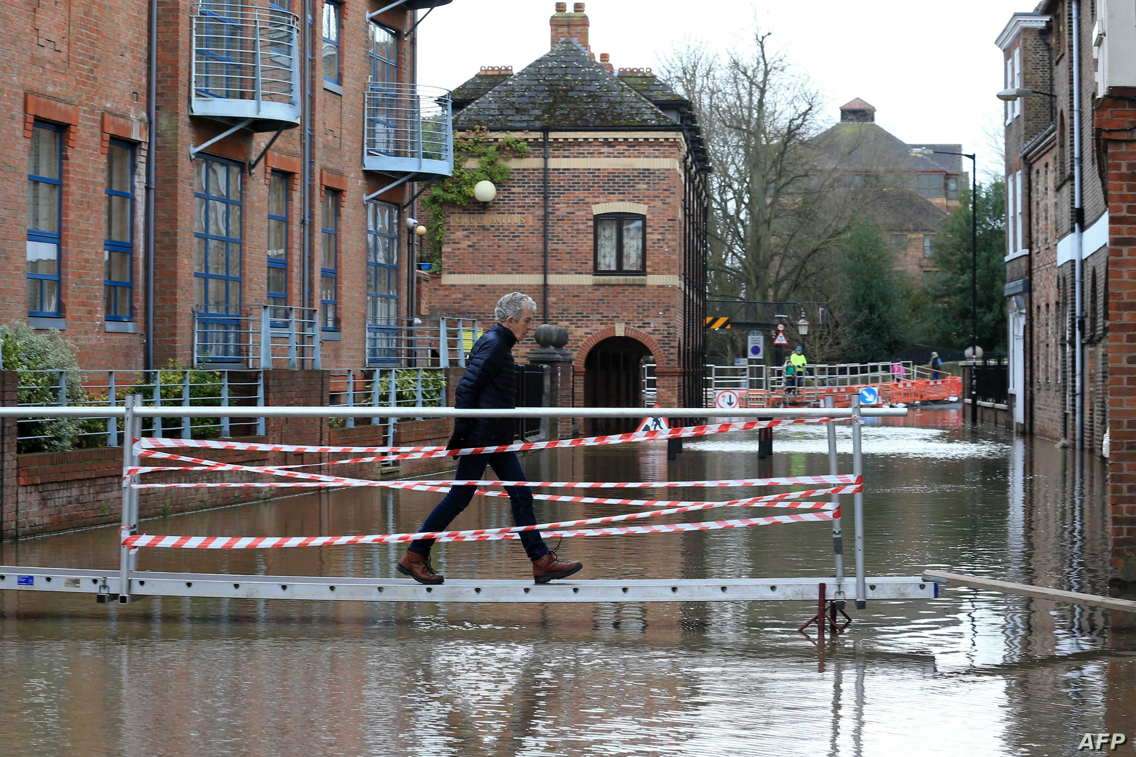 A woman walks on a raised walkway over floodwater after the River Ouse burst its banks in York, northern England, on February…