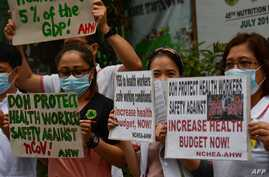 Health workers wearing protective masks carry placards as they hold a protest in front of a government hospital in Manila on…