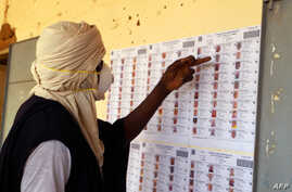 A voter wearing a mask checks the voters role at a polling station during the parlimentary elections in Gao, Mali, on March 29,…
