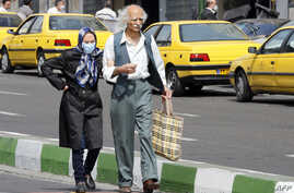 An elderly man and a woman, wearing a protective mask, walk along a street in Iran's capital Tehran on March 15, 2020. - Iran…