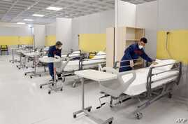 (FILES) A file photo taken on March 21, 2020 shows Iranian workers setting up a makeshift hospital inside the Iran Mall,…