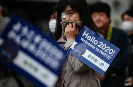 People queue to see the Tokyo 2020 Olympic flame on display outside the railway station in Tono, Iwate prefecture on March 22,…