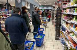Cutomers queue to pay their food and essential products in a supermarket of Milan centre on late March 7, 2020 after Italy…