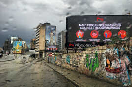 TOPSHOT - A picture taken on March 17, 2020, shows a billboard displaying protective measures against the Coronavirus in the…