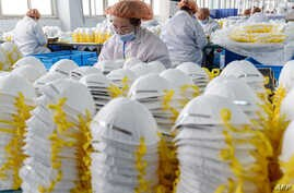 This photo taken on February 28, 2020 shows workers producing face masks at a factory in Handan in China's northern Hebei…