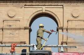 A firefighter sprays disinfectant in front of the India Gate during a government-imposed nationwide lockdown as a preventive…