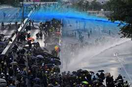(FILES) In this file photo taken on September 15, 2019, pro-democracy protesters react as police fire water cannons outside the…