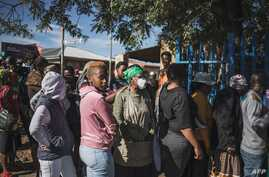 An elderly wears a face mask as she joins informal traders and waste-pickers queueing during a food distribution outside the…