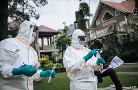 Staff members of the Congolese Ministry of Health perform a COVID-19 test at a private residence in Goma, northeastern…