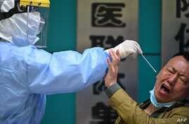 TOPSHOT - A man being tested for the COVID-19 novel coronavirus reacts as a medical worker takes a swab sample in Wuhan in…