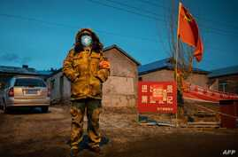 This photo taken on April 21, 2020 shows a staff member keeping watch at a checkpoint in the border city of Suifenhe, in China…