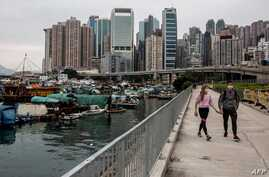A couple (R) walks along the promenade on victoria harbour in Hong Kong on April 25, 2020. (Photo by ISAAC LAWRENCE / AFP)
