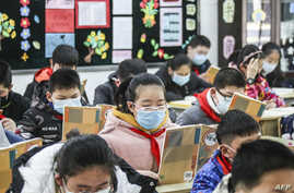 Elementary school students wearing face masks attend a class as they return to school after the start of the term was delayed…