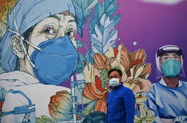 TOPSHOT - A man wearing a face mask walks in front of a mural at the Leishenshan Hospital that had offered beds for coronavirus…