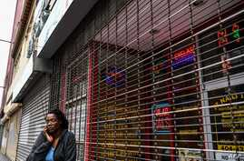 A woman talks on the phone as she stands outside of a closed nail parlour and spa salon in downtown Atlanta, Georgia, on April…