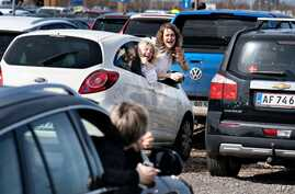 Young people react during the drive-in Eastern service at the parking lot at Aalborg Airport on April 12, 2020 amid the spread…