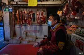 A vendor wearing a face mask waits for customers at a meat stall in Wuhan in China's central Hubei province on April 18, 2020. …