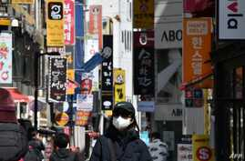 A woman wearing a face mask walks through a shopping district in Seoul on April 23, 2020. - South Korea's economy saw its worst…