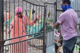 A volunteer from the Rays of Light NGO (R) delivers food and cleaning products to an elderly woman (L) living alone in…