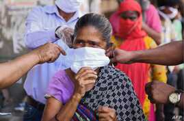 Volunteers of the Diocese of Amritsar Church of North India distribute facemasks to people during a government-imposed…