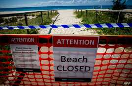 A closed beach signage is seen at Coolangatta Beach on the Queensland - New South Wales border in Brisbane on April 15, 2020. -…