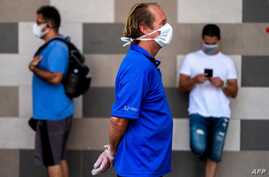 TOPSHOT - People wear face masks to protect against the coronavirus as they keep their distance in a queue at a supermarket…