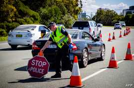A Queensland police officer moves a stop sign at a vehicle checkpoint on the Pacific Highway on the Queensland - New South…