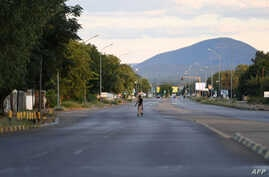 A pedestrian walks across an empty road, which usually experience heavy traffic in Gaborone on April 5, 2020 during the third…