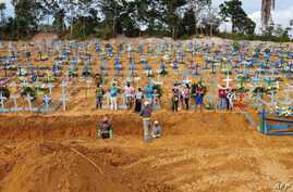 TOPSHOT - Aerial picture showing a burial taking place at an area where new graves have been dug up at the Nossa Senhora…