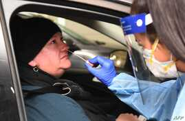 Medical staff perform a test for the COVID-19 coronavirus on a driver at a drive-through testing site in a Melbourne carpark on…