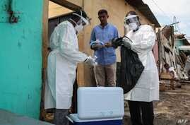 Staff members of the Ministry of Health visit residents to take samples during the first day of mass testing of the COVID-19…
