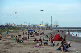Beachgoers enjoy a day of sunshine at Galveston Beach on May 2, 2020 in Galveston, Texas, amid the coronavirus pandemic. -…