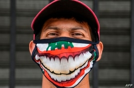 A street vendor wearing a face mask poses outside the central market in San Salvador on May 6, 2020, amid the COVID-19…
