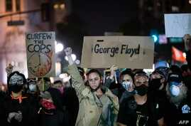 """Demonstrators attend a """"Sit Out the Curfew"""" protest against the death of George Floyd who died on May 25 in Minneapolis whilst…"""