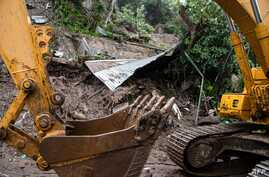 A bulldozer digs and removes debris during the search for seven people who were buried by a landslide due to the heavy rains…