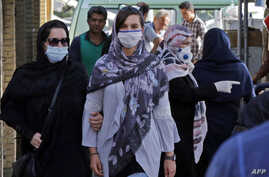 Iranians, some wearing face masks, walk at a market in the capital Tehran on June 3, 2020, amid the novel coronavirus pandemic…